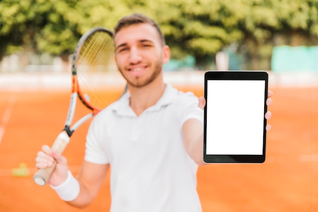 Athletic young tennis player showing a tablet
