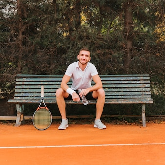 Athletic young tennis player sitting in a bank