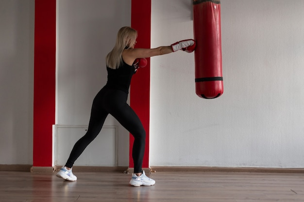Спортивная молодая блондинка женщина в черной футболке в черных спортивных леггинсах в кроссовках в красных боксерских перчатках стоит и бьет боксерскую грушу в тренажерном зале