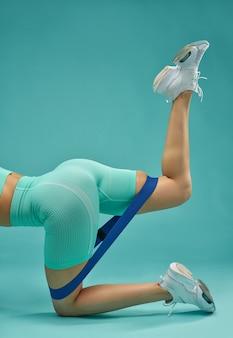Спортивная (ый) молодая женщина делает упражнения с лентой сопротивления