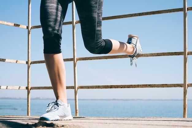 朝の足の運動を行う運動の若い女性、海のクローズアップ