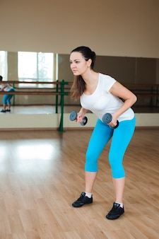 Athletic young woman doing exercises with dumbbells in the gym
