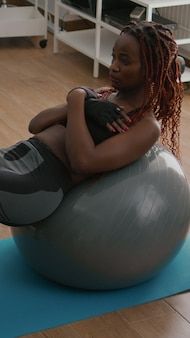 ヨガスイスボールに座って腹筋を行使するリビングルームで朝のフィットネストレーニングをしている運動の若い女性