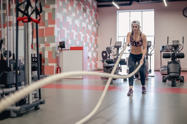 Athletic young woman doing some cross fit exercises with a rope