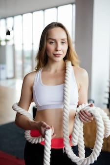 屋外のロープでいくつかのcrossfit演習を行う運動の若い女性