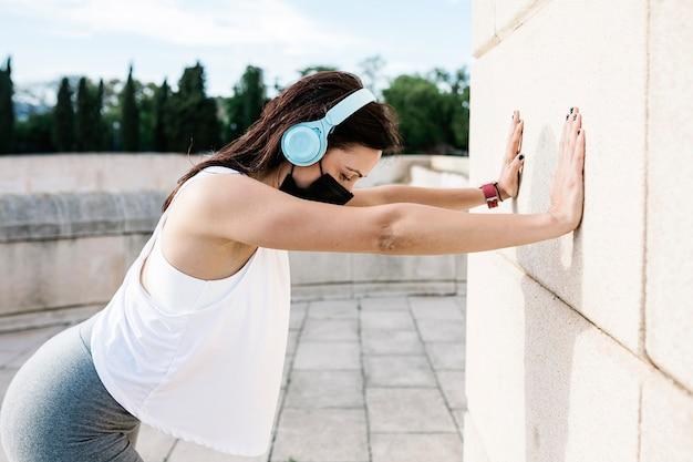 屋外で防塵マスクを着用しながらストレッチ運動をしている運動の若い女性