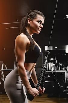 Спортивная (ый) молодая женщина делает упражнения на трицепс на терьере в тренажерном зале