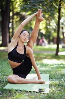 午前中に公園でヨガをしている運動の若い女性。