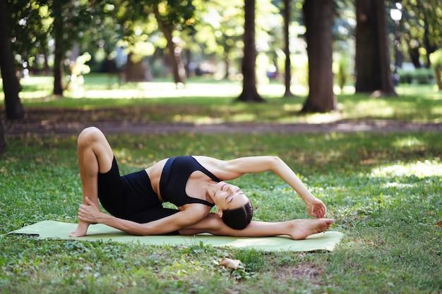 Giovane donna atletica che fa yoga nel parco al mattino, formazione delle donne su una stuoia di yoga