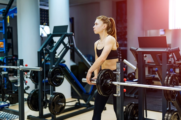 Спортивная (ый) молодая женщина, тренирующаяся в тренажерном зале