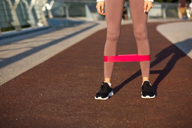 朝の橋でフィットネスガムで運動している運動の若い女性。テキスト用の空き容量
