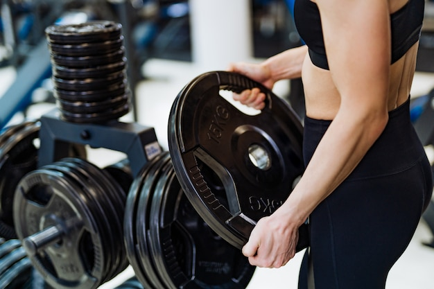 Athletic young woman holding disc from barbell and exercising in gym.