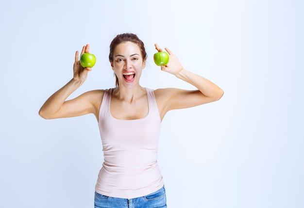 Спортивная (ый) молодая женщина, держащая зеленые яблоки