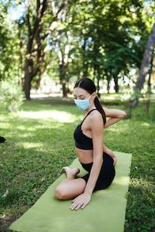 医療用防毒マスクを着用した運動の若い女性、午前中に公園でヨガをしている、ヨガマットでの女性のトレーニング