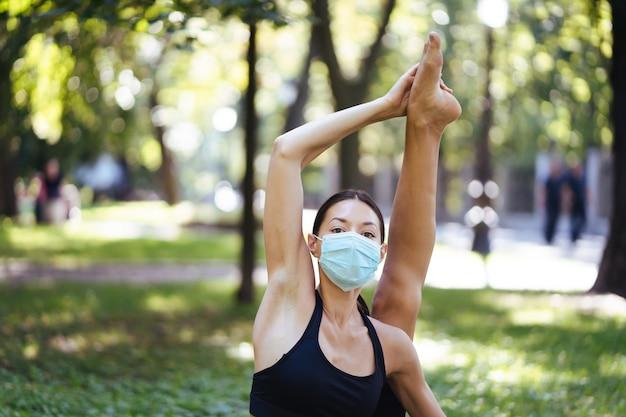 의료 보호 마스크에 운동 젊은 여자, 아침에 공원에서 요가, 요가 매트에 여성의 훈련