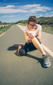 Спортивная (ый) молодая женщина в спортивной одежде, касаясь ее колена болезненной травмой во время тренировки на открытом воздухе. концепция спортивных травм.