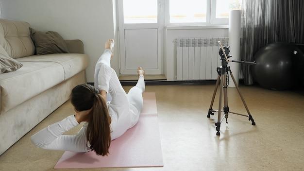 白いスポーツウェアの運動の若い女性は、明るい部屋で三脚にスマートフォンでマット撮影ビデオガイダンスのスポーツ演習を行います