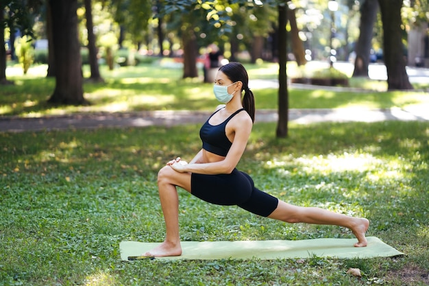 Athletic young woman in a medical protective mask, doing yoga in the park in the morning, women's training on a yoga mat