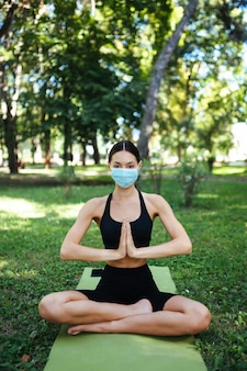 Giovane donna atletica in una maschera protettiva medica, facendo yoga nel parco al mattino