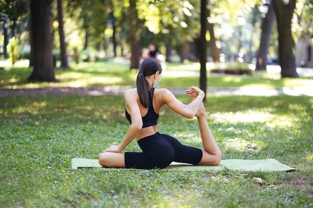 Giovane donna atletica in una maschera protettiva medica, facendo yoga nel parco