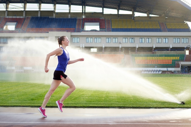 Athletic young woman in pink sneakers run near sprinkler on running track stadium
