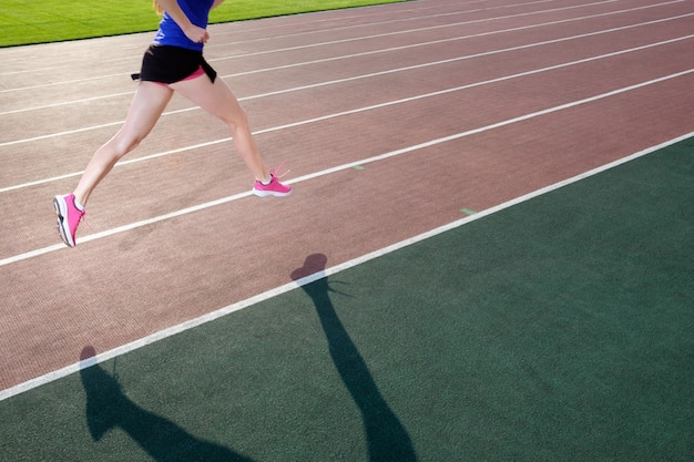 Athletic young woman in pink sneakers run on running track stadium