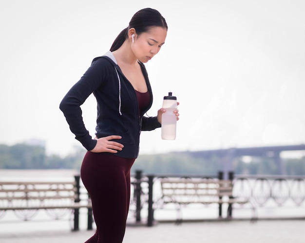 Атлетик молодая женщина готова тренироваться на открытом воздухе