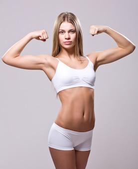 Спортивная (ый) молодая женщина работает на белом фоне, вид сбоку
