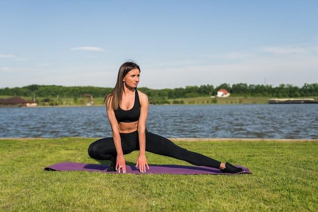 ハムストリングを伸ばす運動の若い女性、湖のビーチで外でトレーニングする前に脚はトレーニングフィットネスを行使します