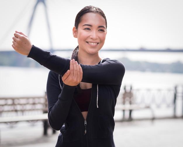 Атлетик молодая женщина, растяжения на открытом воздухе