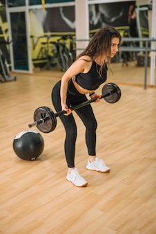 Athletic young woman training with barbells in gym