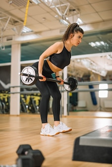 Athletic young woman training with barbells