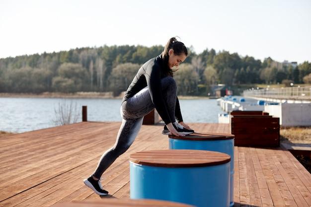 Атлетик молодая женщина с тонированное красивое тело тянется перед выполнением упражнений. спортсмен разогревается и готовится к тренировкам