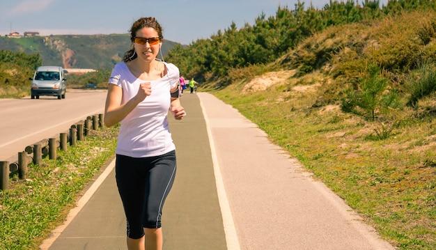 Спортивная (ый) молодая женщина с наушниками, слушая музыку со своего смартфона во время бега на взлетно-посадочной полосе на открытом воздухе. концепция современного здорового образа жизни.