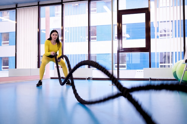 Athletic young woman with ropes for cross fit training in fitness gym.