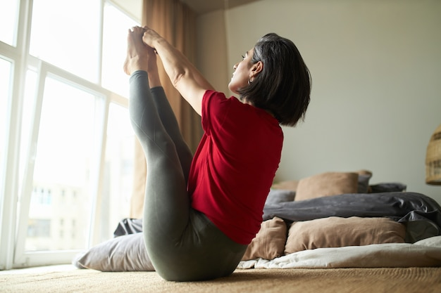 Athletic young woman with strong fit body practicing yoga in bedroom, sitting upward facing intense stretch pose