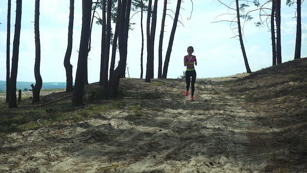 Athltic young woman in sports uniform running around the forest outdoors