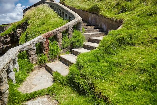 緑の丘の斜面に古い石の階段がある大西洋の海岸線