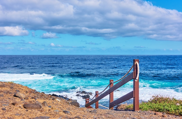 Atlantic ocean and rocky coast of tenerife island with footpath to the water, the canaries