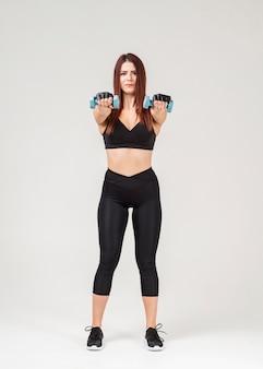 Вид спереди женщины в atleisure, осуществляющих с весами