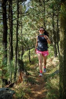 Atleta corriendo en un sendero de la montana rodeada de arboles