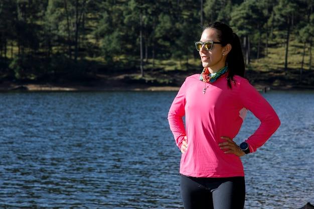 Атлета descansando en la orilla de un lago despues de correr en el bosque rodeado de arboles