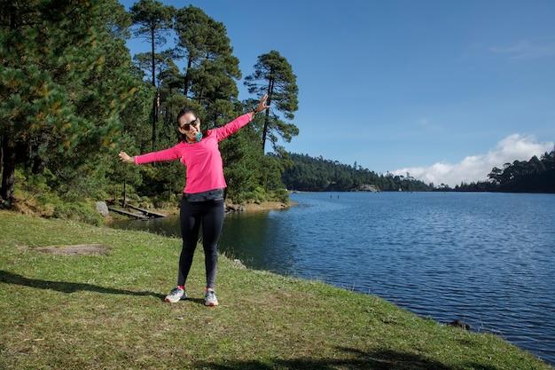 Atleta estirando despues de correr a la orilla de un lago