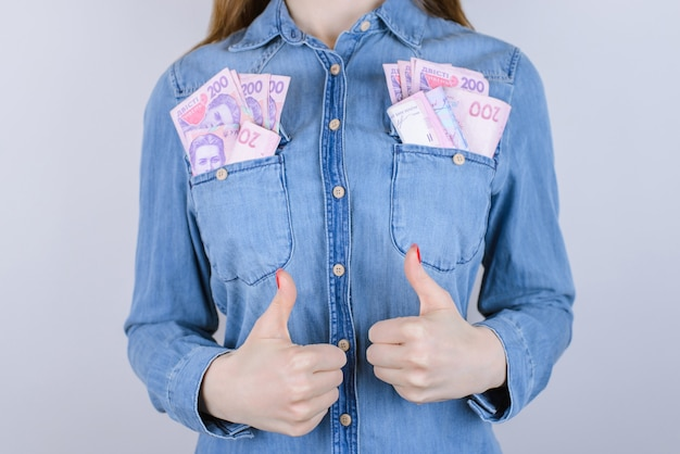 Банкомат дело стек джинсы человек люди хорошо экономика студент весело шутка смешная концепция. обрезанное крупным планом фото взволнованной жизнерадостной уверенной умной леди, делающей большие пальцы руки вверх с большим количеством карманов с деньгами, изолированный фон