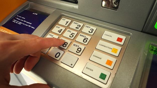 Atm機とクローズアップの男性の手が暗証番号ボタンを押してクレジットを引き出します。