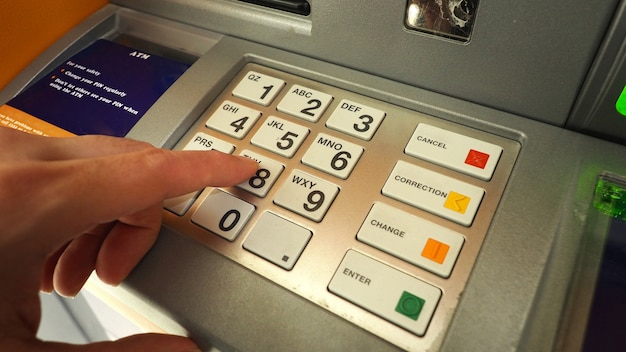 Atm machine and close-up man hand pushing on the pin number button to withdraw the money credit.