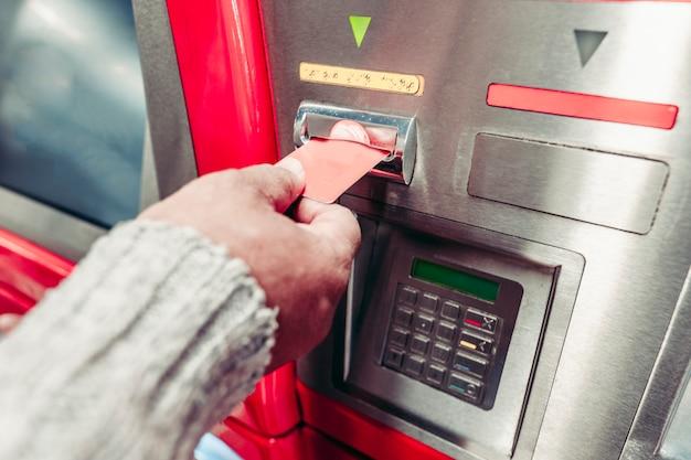 銀行のクレジットカードでatmからお金を引き出す男の手