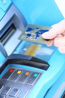 男性の手は、atmに対してゴールデンクレジットカードを保持します。