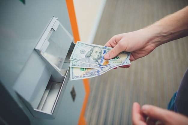 手の男はatmマシン、銀行、金融の概念にカードを挿入します