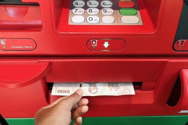 Atmマシンからお金を受け取る手。